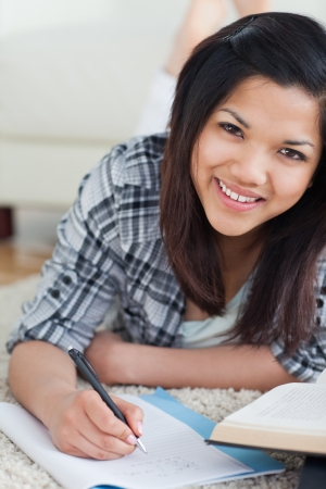 Smiling woman on the floor writing on a notebook in a living room Stock Photo - 16207802