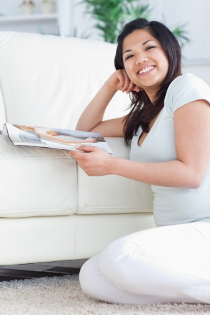 Smiling woman on her knees while holding a magazine in a living room Stock Photo - 16203922