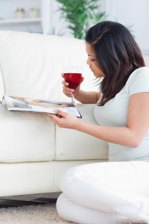 Woman holding up a glass of red wine while reading a magazine in a living room photo