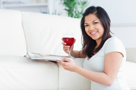 Woman on her knees holding a glass of red wine and a magazine in a living room photo
