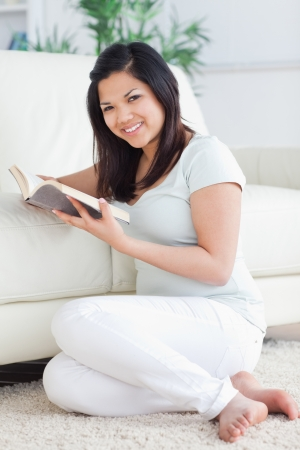 Woman holding a book while sitting in front of a couch in a living room photo