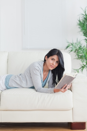 woman holding a book while relaxing on a couch in a living room photo