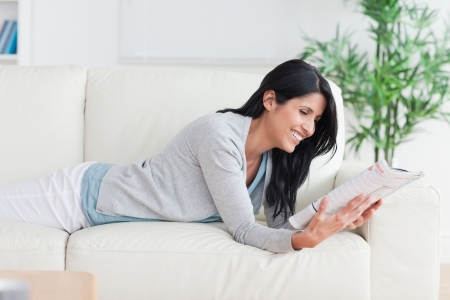 Woman reading a magazine as she lays on a couch in a living room photo