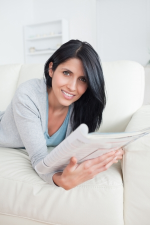 Woman lies on a couch and holds a magazine in a living room photo