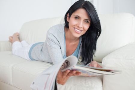 Woman holding a magazine while laying on a couch in a living room Stock Photo - 16203835
