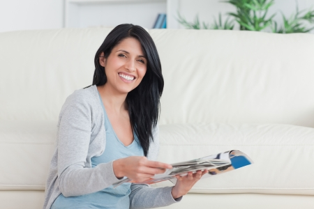 Smiling woman holding a magazine while leaning on a couch in a living room photo