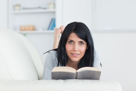 Woman holding a book while resting on a couch in a living room photo