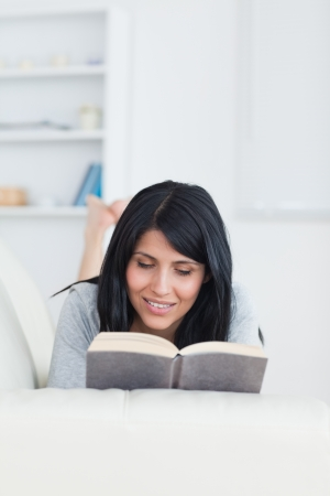 Woman reading while lying on a couch in a living room Stock Photo - 16203054