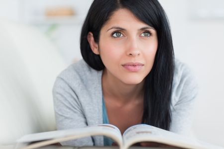 Mujer sosteniendo un libro en sus manos mientras está acostado en un sofá en una sala de estar Foto de archivo
