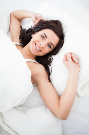 awaken: Smiling woman lying while stretching her body in her bedroom