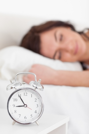 nightstand: Alarm clock being placed on a nightstand in a bedroom Stock Photo
