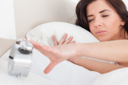 turning table: Brunette woman turning off her alarm clock in her bedroom Stock Photo