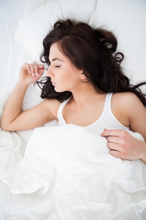 Brunette woman napping while lying under her quilt in her bedroom photo