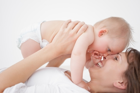 Happy mother holding her daughter while lying indoors photo