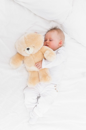 Baby sleeping while holding a teddy bear in a bedroom photo