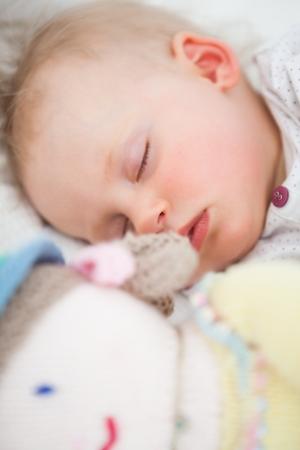 Cute baby sleeping next to her stuffed teddy bear in a bedroom photo