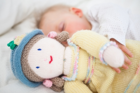 Baby sleeping while holding a plush doll in a bedroom photo