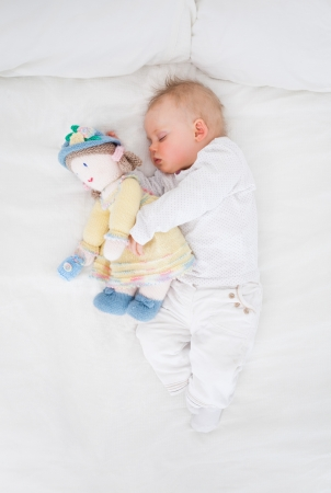 Baby sleeping while embracing a plush doll in a bedroom photo