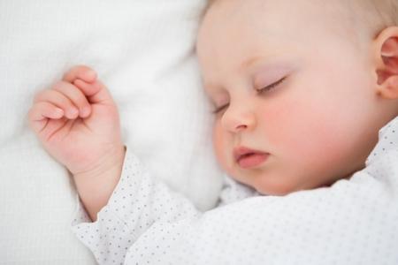 niemowlaki: Spokojne dziecko leżące na łóżku podczas snu w jasnym pomieszczeniu
