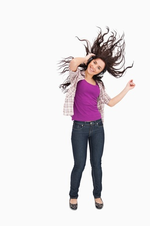 Brunette listening to music with her hair in the hair against white background photo
