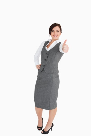 thumbup: Happy well-dressed woman the thumb-up against white background