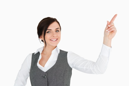 welldressed: Smiling well-dressed brunette pointing up against white background Stock Photo