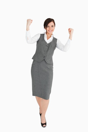 Woman in grey suit walking the fists raised against white background Stock Photo - 16200387