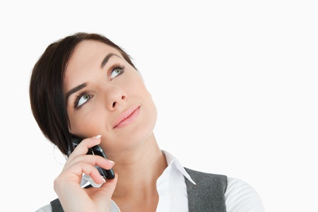 Beautiful businesswoman looking up while phoning against white background