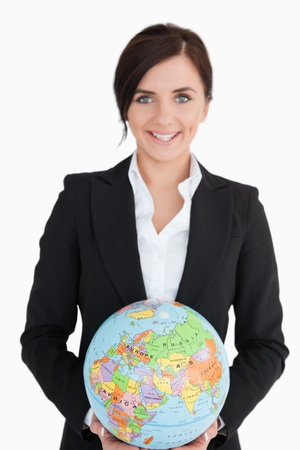 Smiling woman in suit holding an earth globe against white background photo
