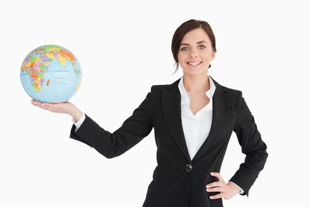 Smiling businesswoman holding an earth globe in her palm against white background photo