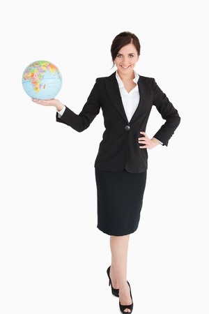 Happy businesswoman holding an earth globe against white background photo