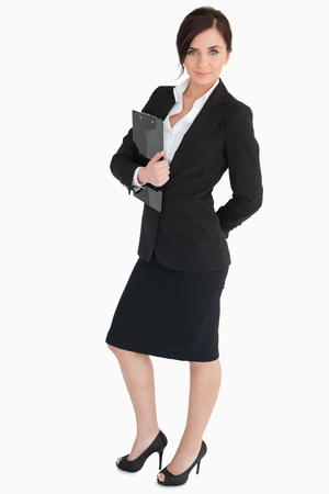 Attractive businesswoman holding a clipboard against white background photo