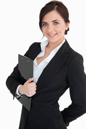 Happy businesswoman holding a clipboard against white background photo