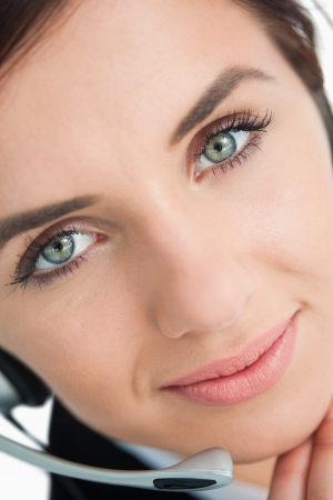 Blue eyed woman with headset in close-up photo