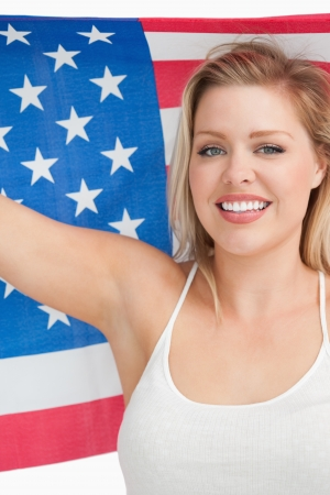 old glory: Smiling woman holding the Old Glory flag in a studio