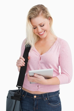 Happy blonde woman holding her tablet pc against a white background Stock Photo - 16205005