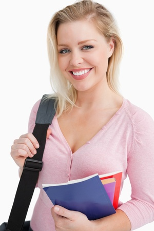 Smiling young woman holding school books against a white background Stock Photo - 16204384