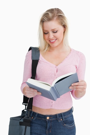Smiling blonde woman reading a novel against a white background Stock Photo - 16206672