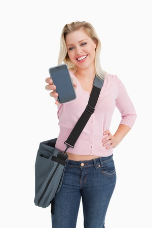 Happy blonde woman showing her smartphone against a white background photo