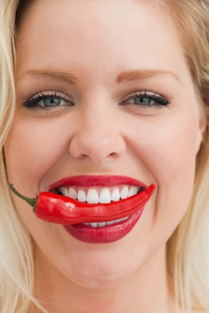 Close-up of a cheerful blonde woman placing a chili between her teeth photo