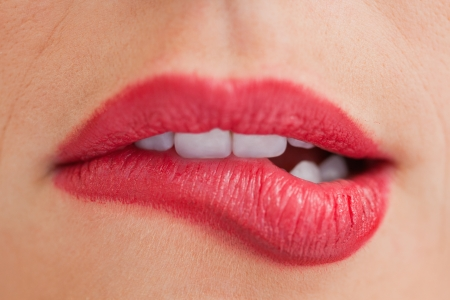 Close-up of an attractive woman biting her beautiful lips photo