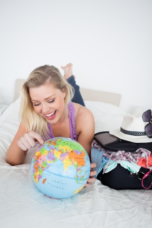 Student with a suitcase pointing on a globe while lying on her bed Stock Photo - 16204805
