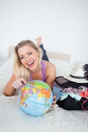 Student with a suitcase pointing on an earth globe while lying on her bed Stock Photo - 16204602