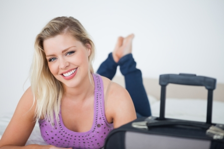 Beautiful woman with a suitcase lying on her bed Stock Photo - 16204493