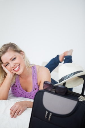 Young woman smiling behind a suitcase lying on her bed photo