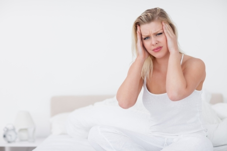 Blonde with a headache sitting on her bed Stock Photo - 16202117