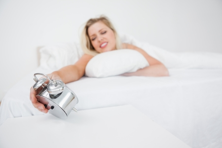 Woman looking at her alarm clock while lying in her bed photo