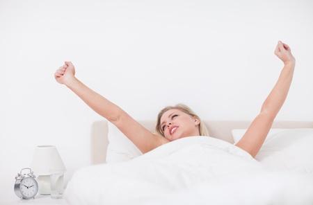woman bed: Mujer joven que estira en la cama