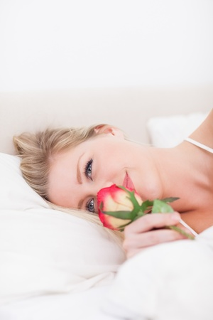 Blue eyed woman smelling a rose in he bed photo