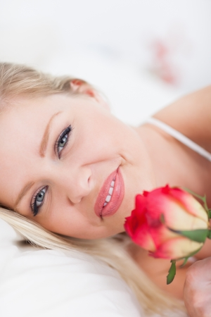 Blue eyed woman with a rose in a bed photo